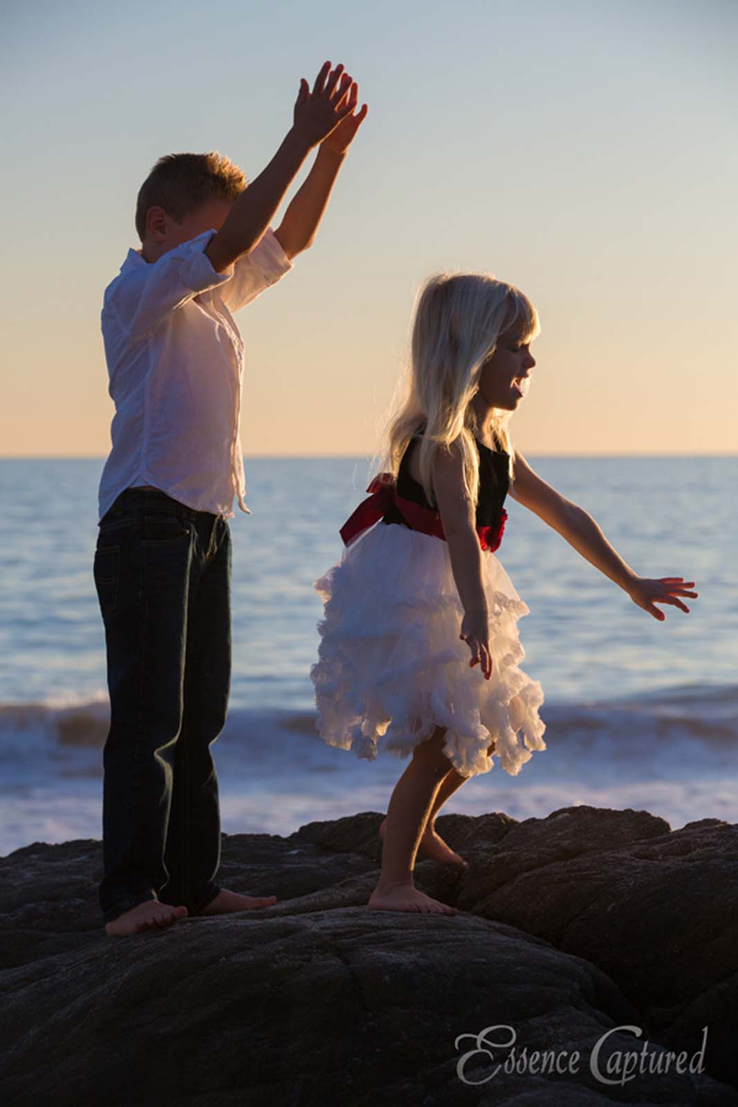 two children playing at beach jumping on rocks boy girl blonde dressed up sunset ocean